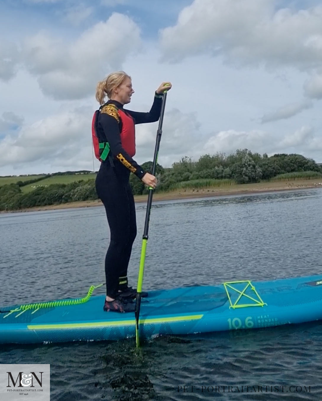 Melanie standing on a paddle board!